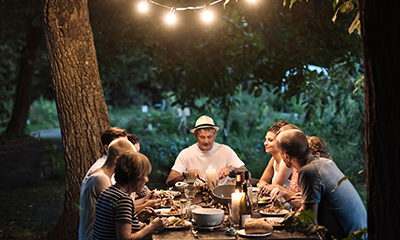 Family having a dinner all together at a garden anew landscaping trend